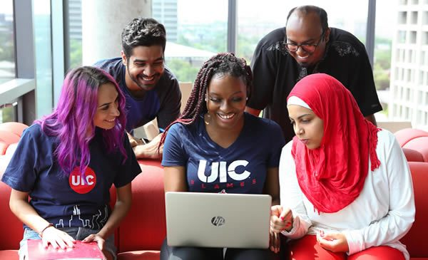 Group of students looking at laptop.
